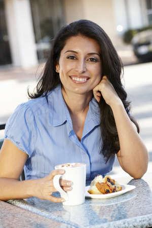 Hispanic woman sitting at sidewalk caf� photo