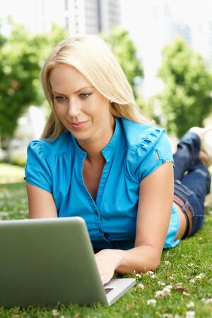Woman using laptop in city park Stock Photo - 11217592