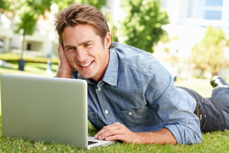 Man using laptop in city park photo