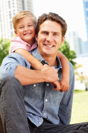 Man sitting in city park with young son photo