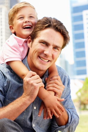 dad and child: Man sitting in city park with young son Stock Photo