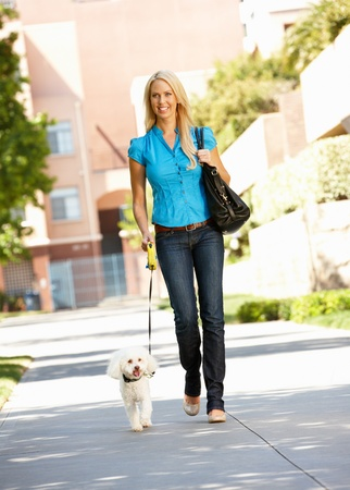 Woman walking with dog in city street photo