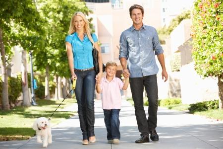 都市通りで犬を連れて歩いて家族