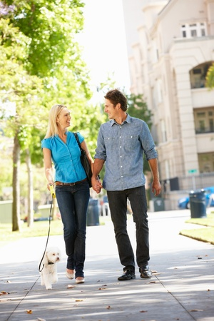 Couple walking with dog in city street photo