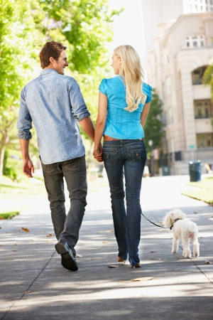 people walking street: Couple walking with dog in city street Stock Photo