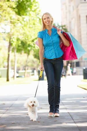 strolling: Woman on shopping trip with dog