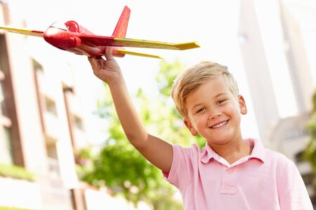 plane tree: Young boy outside with toy aeroplane