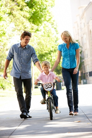 3 4 length: Parents with boy on bike Stock Photo