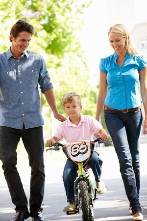 guiding: Parents with boy on bike Stock Photo