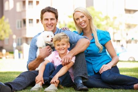 Pareja en el parque de la ciudad con el hijo y el perro