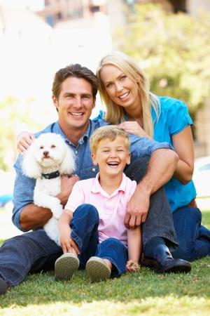 familia abrazo: Pareja en el parque de la ciudad con el hijo y el perro Foto de archivo