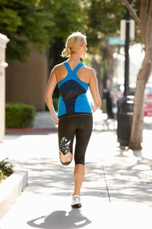 Woman running on city street photo