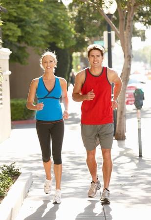 Couple running on city street photo