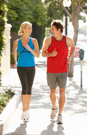 Couple running on city street photo