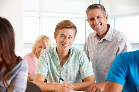 Tutor helping student in class photo