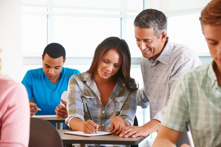 teaching and learning: Tutor helping student in class
