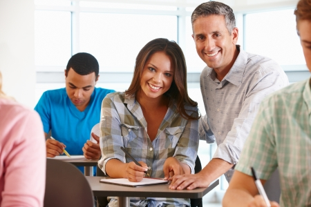 teacher teaching: Tutor helping student in class