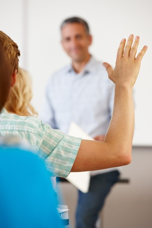 adult classroom: Student with hand up in class