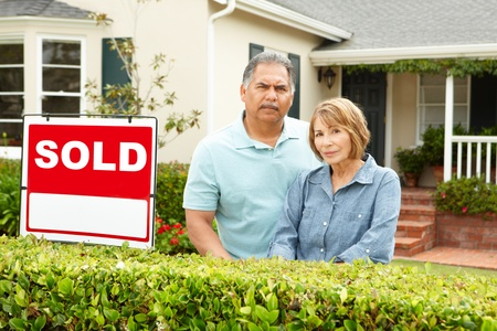 sold: Senior Hispanic couple outside house with sold sign Stock Photo