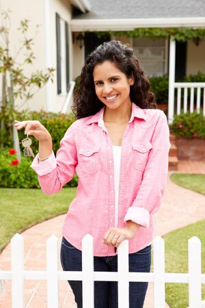 well maintained: Young Hispanic woman outside new home