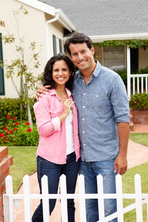 first home: Hispanic couple outside new home Stock Photo