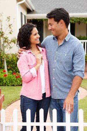 Hispanic couple outside new home photo