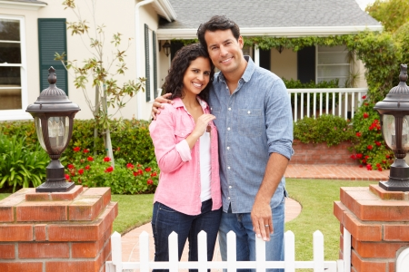 home keys: Hispanic couple outside new home Stock Photo