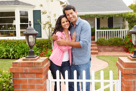 front of house: Hispanic couple outside home Stock Photo