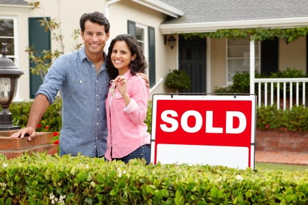 Pareja de hispanos fuera de la casa se vende con el signo Foto de archivo