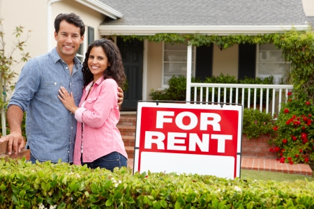 for rent sign: Hispanic couple outside home for rent