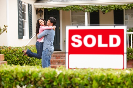 home garden: Hispanic couple outside home with sold sign