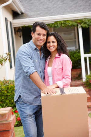 removals: Hispanic couple moving into new house Stock Photo