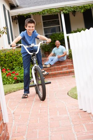 Boy and grandfather at home with bike photo