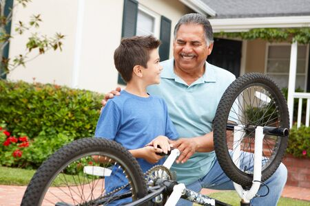 helping people: boy and grandfather fixing bike