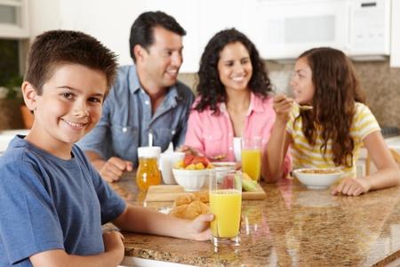 drinking juice: Hispanic family eating breakfast Stock Photo