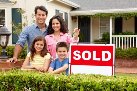 Hispanic family outside home with sold sign photo