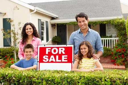 well maintained: Hispanic family outside home with for sale sign