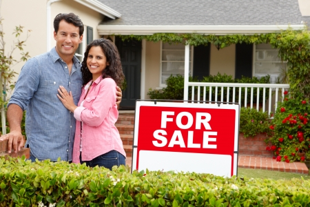 selling house: Hispanic couple outside home with for sale sign Stock Photo