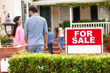 home for sale: Famiglia ispanica fuori casa con il segno per la vendita Archivio Fotografico