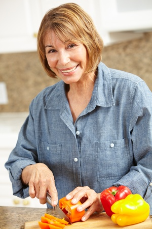 Mid age woman chopping vegetables photo