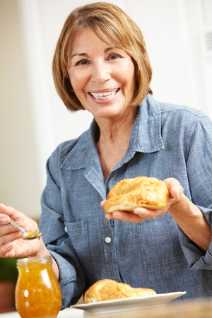 Mid age woman eating croissants photo