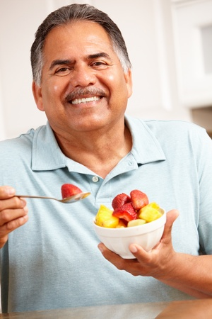 man eten: Senior man het eten van fruit