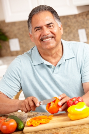 one senior adult man: Senior man chopping vegetables Stock Photo