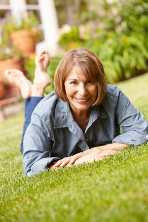 Mid age woman relaxing in garden photo