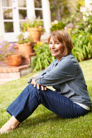 the fifties: Mid age woman relaxing in garden