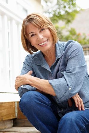 50s women: Mid age woman relaxing in garden