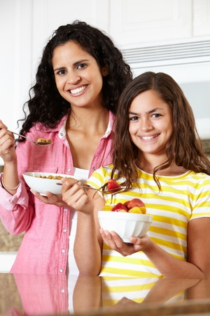 Mother and daughter eating cereal and fruit photo