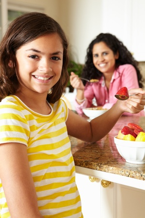 11 year old girl: Mother and daughter eating cereal and fruit Stock Photo