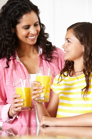 Mother and daughter drinking orange juice photo