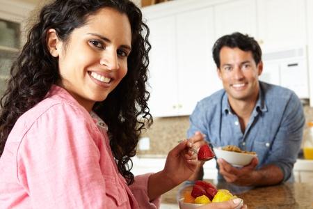 pareja comiendo: Pareja hispana de comer cereales y fruta